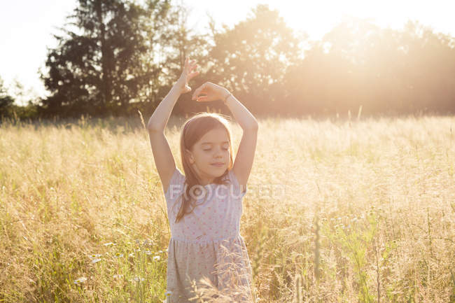 Young girl standing in field at summer evening — Stock Photo