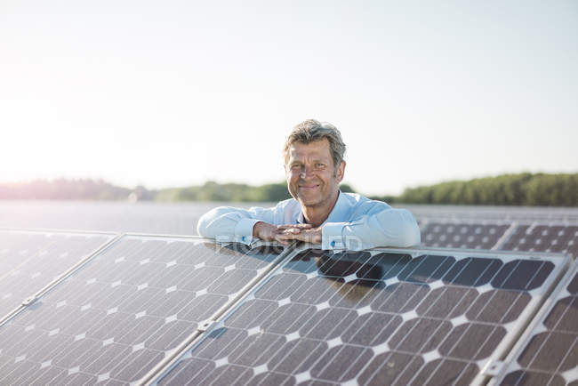 Smiling mature man standing in solar plant — Stock Photo