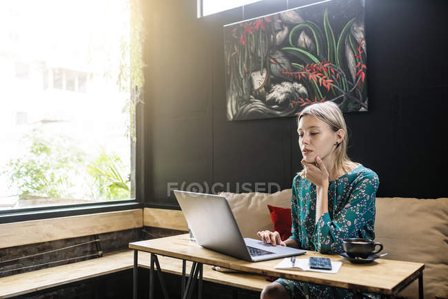 Young woman with green dress sitting in cafe, working on her laptop — Photo de stock