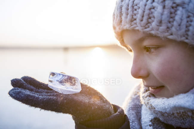Germany, Brandenburg, Lake Straussee, portrait of a girl standing on frozen lake, looking at piece of ice on her hand — Stock Photo