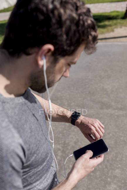 Sportive man with cell phone, earphones and smartwatch outdoors — Stock Photo
