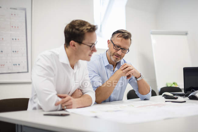 Two businessmen discussing plan on desk in office — Photo de stock