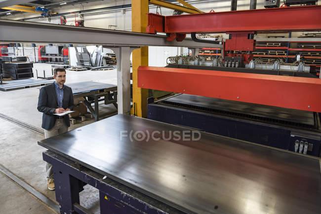 Geschäftsmann schreibt auf Klemmbrett in Fabrikhalle — Stockfoto