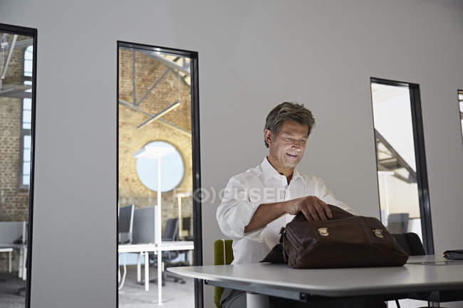 Businessman looking in shining briefcase in conference room of modern office — Stock Photo