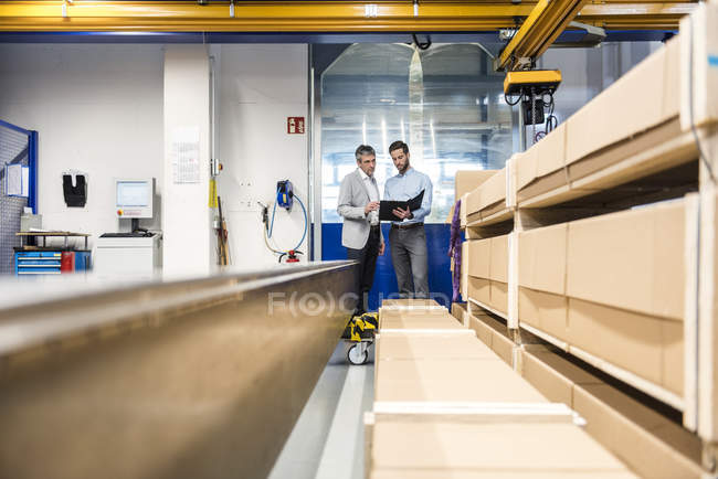 Businessmen during meeting with clipboard in storage — Stock Photo