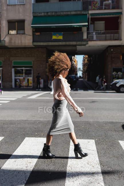 Молодая женщина с афро-прической переходит улицу в городе — стоковое фото