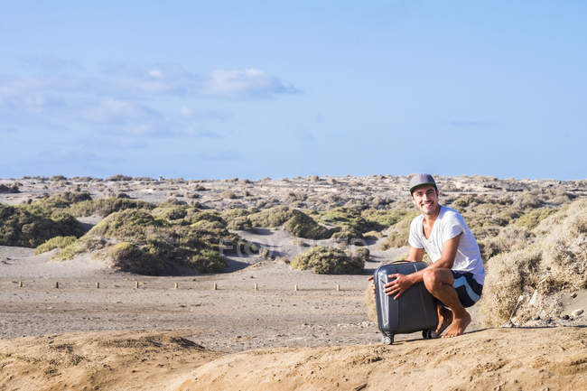 Happy man with rolling suitcase in dune landscape — Stock Photo
