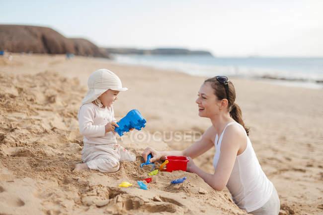 Mère jouant avec petite fille sur la plage — Photo de stock