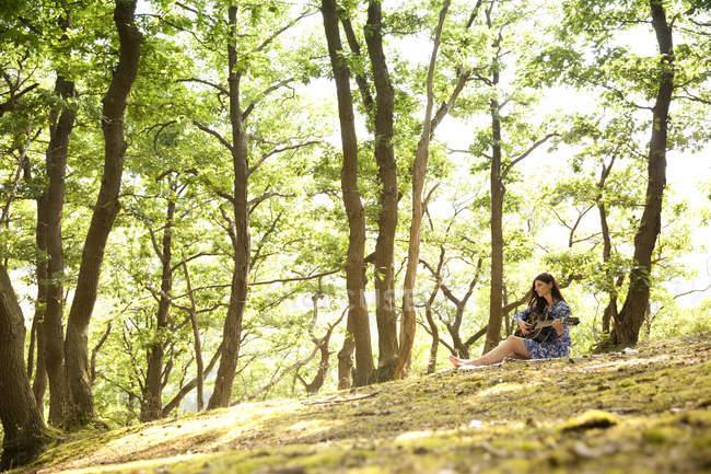 Jeune femme jouant de la guitare dans la forêt — Photo de stock