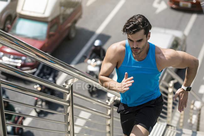 Homem na camisa azul da aptidão que funciona em cima na cidade — Fotografia de Stock
