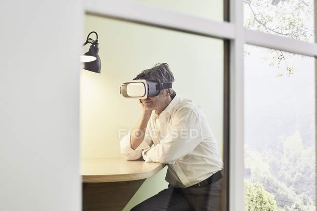 Businessman wearing VR glasses in modern office — Stock Photo