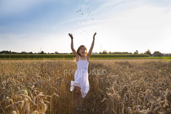 Маленька дівчинка бавиться на пшеничному полі. — стокове фото
