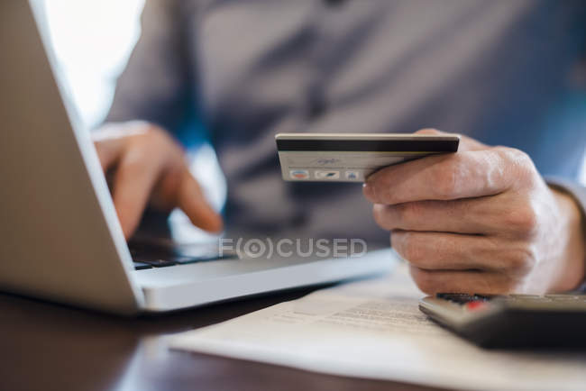 Man using laptop and holding credit card, close-up — Stock Photo