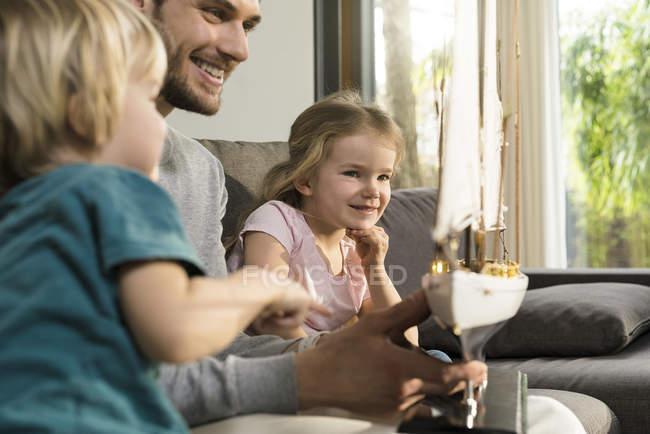 Усміхнений батько і діти дивляться на іграшку модель корабля на дивані будинку — стокове фото