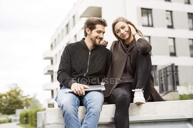 Щаслива пара з ноутбуком в міських навколишніх — стокове фото