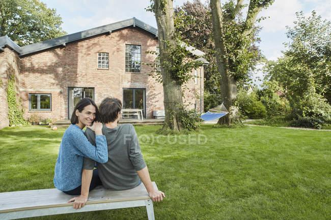 Smiling affectionate couple sitting in garden of their home — Fotografia de Stock