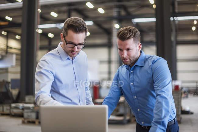 Два бизнесмена делят ноутбук на заводе — стоковое фото