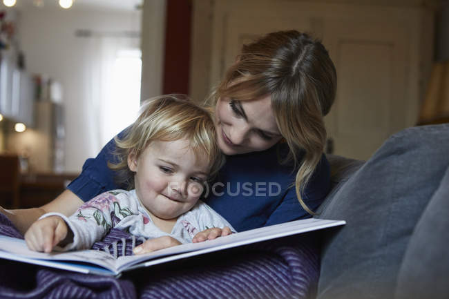 Mother and little daughter sitting on couch at home and looking at book — Photo de stock