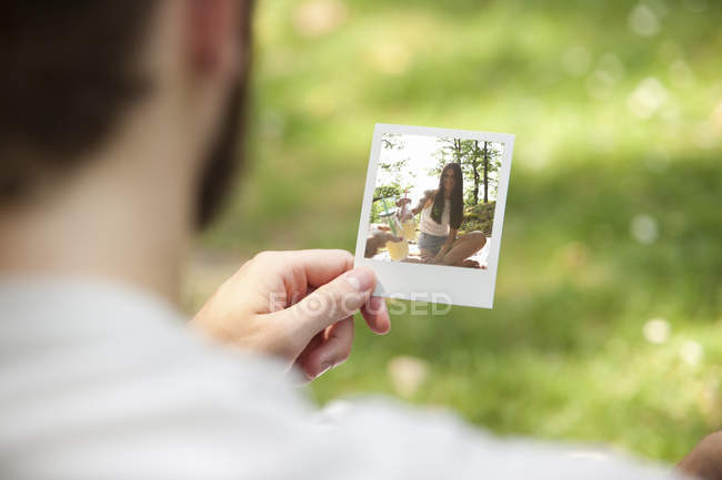 Man holding instant photo of his girlfriend, partial view — Stock Photo