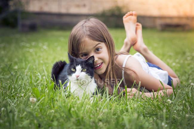 Retrato de niña con gato acostado en un prado - foto de stock