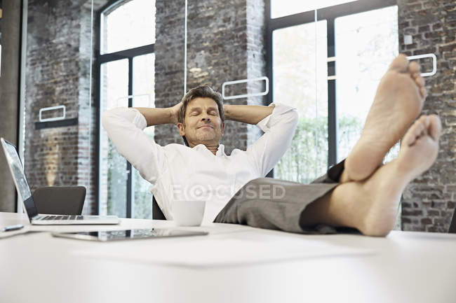Barefooted businessman relaxing in conference room of modern office — Stock Photo