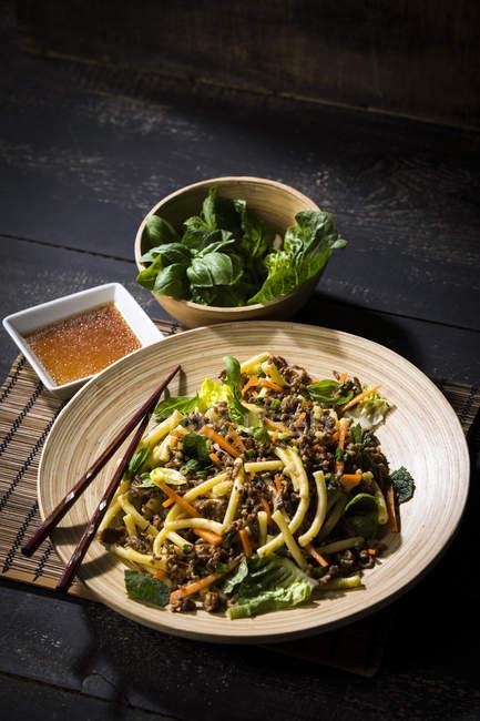Salade de viande hachée asiatique aux macaronis, gingembre, chili, ail, carotte, oignon de printemps, sauce au citron de soja — Photo de stock