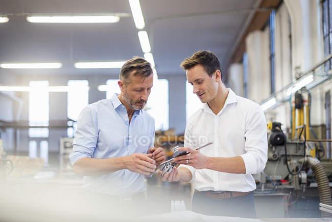 Dos empresarios en fábrica discutiendo el producto - foto de stock