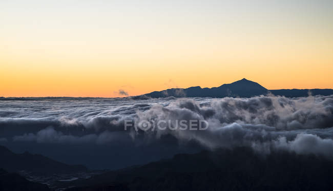 Spain, Canary Islands, Gran Canaria, view from Roque Nublo at sunset with Teide  on Tenerife in background — Stock Photo