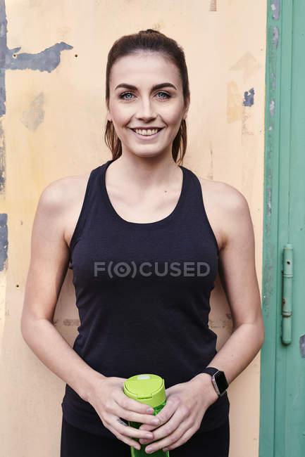 Lächelnde sportliche Frau mit Wasserflasche — Stockfoto