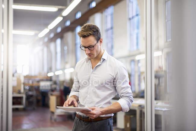 Jeune homme d'affaires en usine utilisant une tablette — Photo de stock