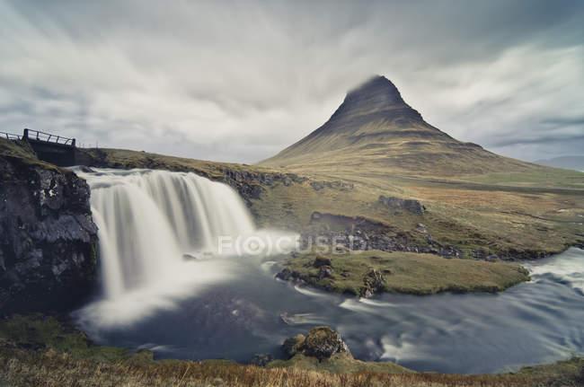 Исландия, водопад Kirkjufellsfoss и Kirkjufell на заднем плане — стоковое фото