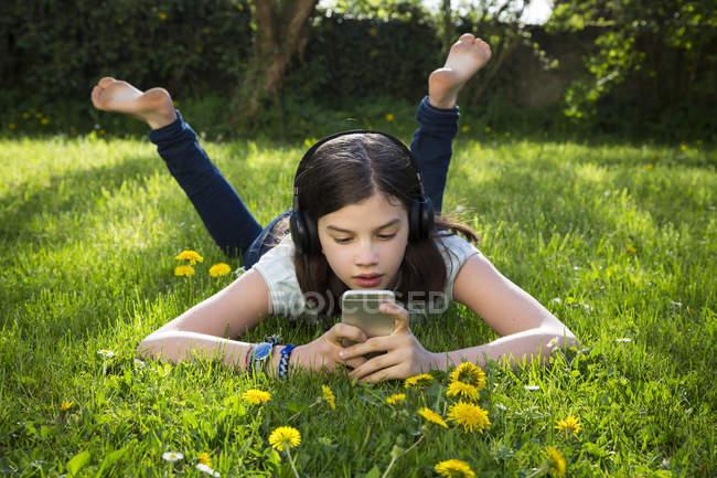 Girl lying on meadow listening music with headphones using smartphone — Stock Photo