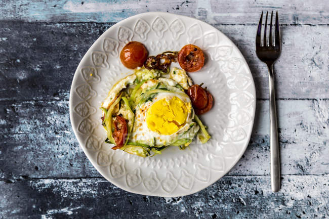 Zoodle nest with egg, zucchini noodles with egg, tomatoes and red onion - foto de stock