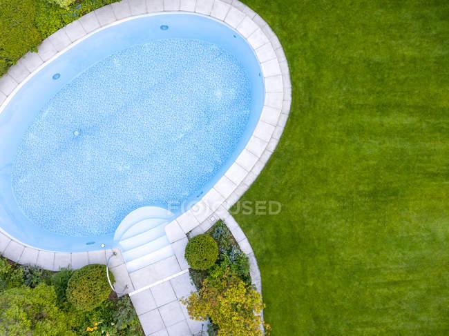 Piscina vacía en jardín, vista superior - foto de stock