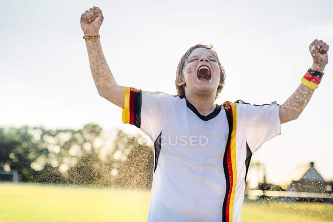 Boy wearing German soccer shirt screaming for joy, standing in water splashes — Stock Photo