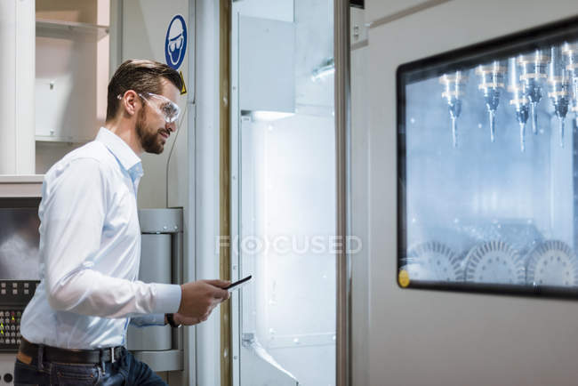 Businessman with tablet wearing safety goggles and examining machine in factory looking — Stock Photo