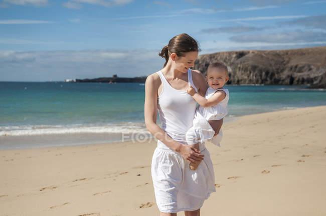 Mère tenant sa petite fille sur la plage — Photo de stock