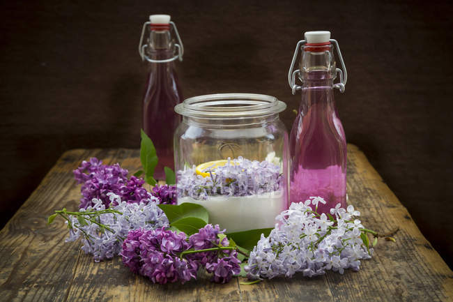 Glass bottles of homemade lilac sirup and ingredients in glass — Stock Photo