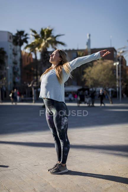 Espanha, Barcelona, mulher que se estende no calçadão — Fotografia de Stock