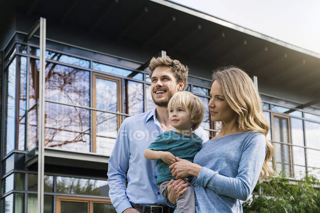 Усміхнені батьки з сином перед їхнім будинком — стокове фото