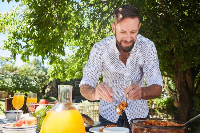 Homme qui distribue des pâtes à la table du jardin — Photo de stock