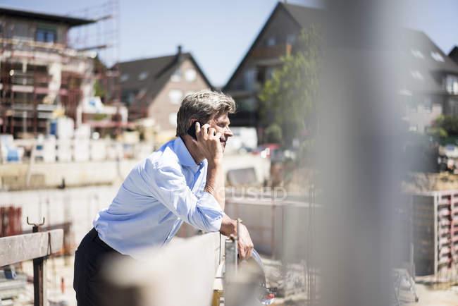 Человек на мобильном телефоне на стройке — стоковое фото