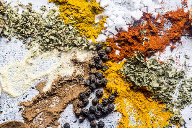 Spices, curry, chilli, cinnamon, curcuma, garlic, parsley, oregano, salt and pepper on wood — Stock Photo