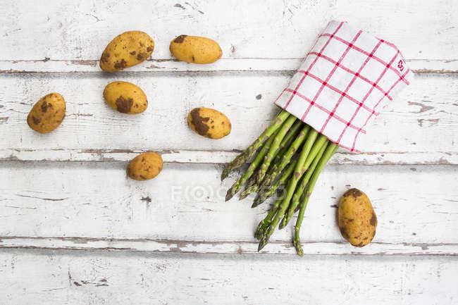 Зеленая спаржа и картофель на белом деревянном фоне — стоковое фото