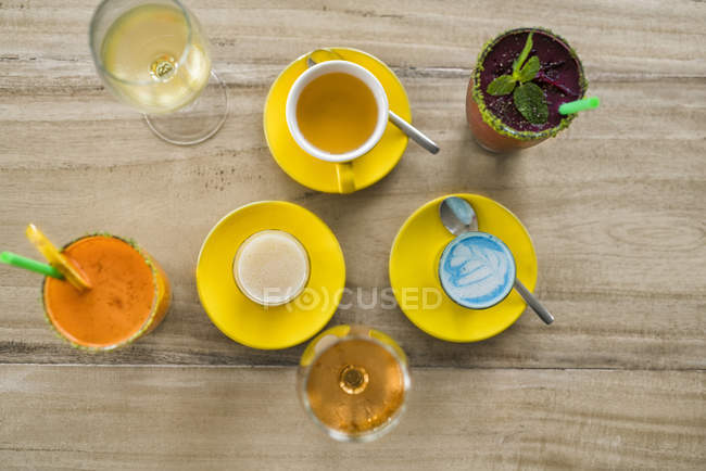 Wooden table with various beverages like smurf latte, smoothie, wine and tea — Stock Photo