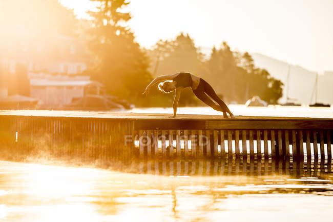 Mujer practicando yoga en embarcadero en el lago - foto de stock