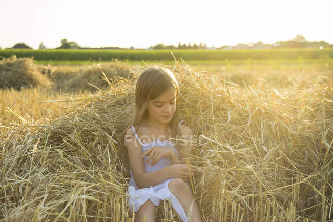 Petite fille assise sur la paille du champ possédé — Photo de stock