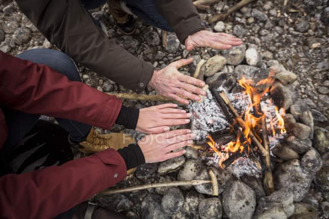 Image recadrée de couple se réchauffant les mains au feu de camp — Photo de stock