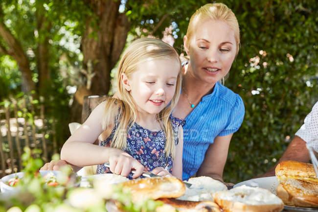 Девушка с матерью завтракают за садовым столом — стоковое фото