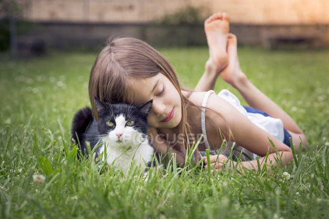 Little girl cuddling with cat on a meadow — Stock Photo